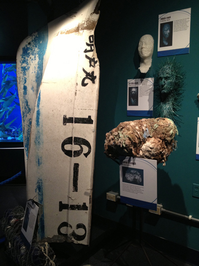 Saving Our Synthetic Seas, a traveling exhibition put together by The 5 Gyres Institute. Pictured from left to right is a Japanese vessel found floating in the North Pacific, masks cast from plastic, and the stomach contents of a camel that ingested rope and plastic bags.